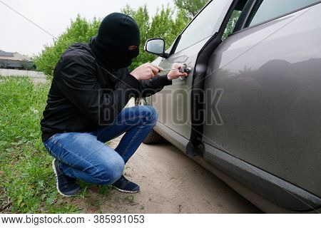 Breaking Into The Car. Theft Auto. The Malefactor In A Black Mask Opens A Door In A Car.