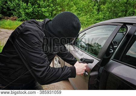 Car Theft In Black Mask With A Gun Opens The Door In The Car