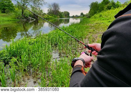 The Hands Of A Fisherman With A Fishing Rod Near The River. Fishing, Process
