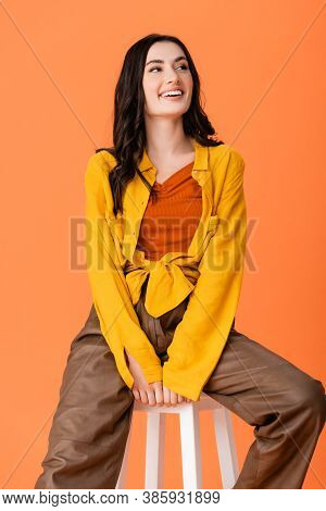 Trendy Woman In Autumn Outfit Sitting On White Stool And Looking Away Isolated On Orange