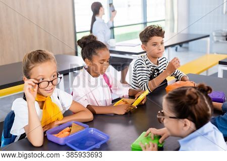 Schoolgirls Talking While Sitting In School Eatery With Multicultural Classmates And Teacher On Back