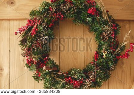 Christmas Wreath Hanging On Rustic Wooden Door In House.