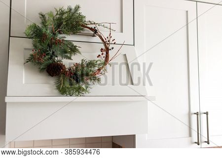 Creative Modern Christmas Wreath Hanging On Stylish Kitchen Cabinets.