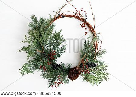Rustic Christmas Wreath Hanging On White Wall Indoors, Festive Holiday Decoration