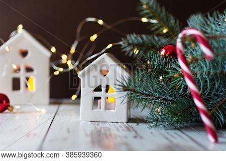 Christmas Candlestick In A House Shape On Wooden Floor Near Fir Tree Over Christmas Lights. Christma
