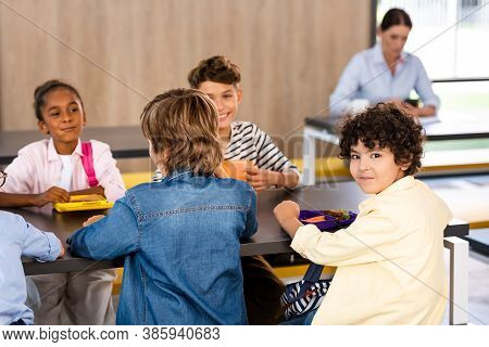 Selective Focus Of Arabian Schoolboy Looking At Camera While Sitting In Dining Room Near Multicultur