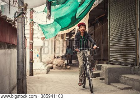 Leh , Ladakh Region , India - August 20, 2016: Tibetan Teenager Boy Rides The Bike On The Leh Narrow