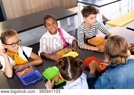 Selective Focus Of African American Schoolgirl Looking At Camera While Sitting In School Eatery Near