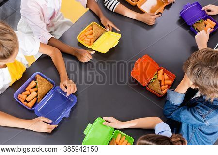 Overhead View Of Multicultural Classmates Sitting In School Eatery Near Lunch Boxes With Fresh Carro