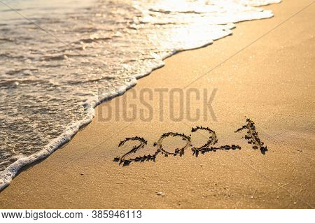 Inscription 2021 On The Seashore. Beach And Sea Wave At Sunset. Concept Of The New 2021.
