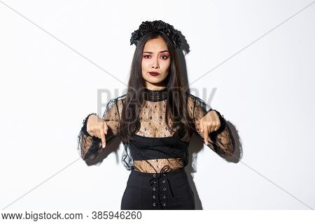 Concerned An Disappointed Asian Woman In Black Lace Dress And Wreath Smirk Skeptical While Pointing