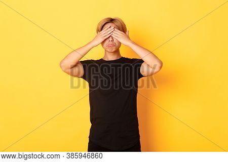 Portrait Of Sad And Miserable Asian Guy Shut Eyes And Sulking Upset, Standing Yellow Background