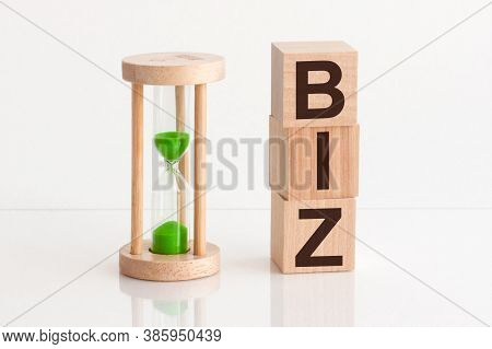 Close-up Of An Hourglass Next To Wooden Blocks With The Text Biz