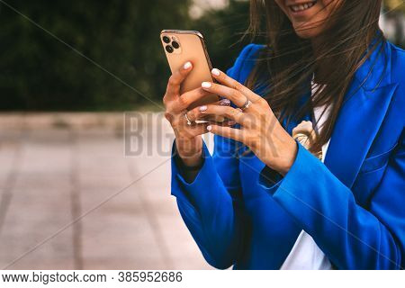 Happy Smiling Business Woman In Blue Blazer Using Smartphone. Professional Female Manager Reading In