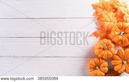 Autumn Background Decoration From Dry Leaves And Pumpkin On  Wooden Background. Flat Lay, Top View W
