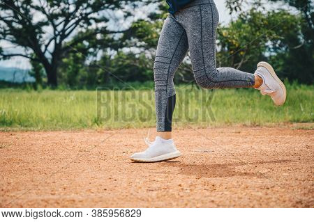 Woman Doing Workout By Running On Dirt Road (or Trail Running). The Benefit When Running On Dirt Roa