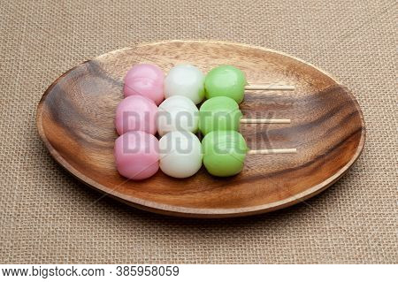 Japanese Traditional Sweet Called Dango Mochi On Wooden Platter With Green Tea. Isolated On Jute Bac
