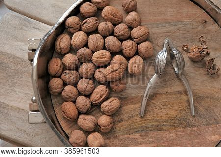 Walnuts And Nutcracker In A Round Silver Platter. View From Above.nutcracker And Nuts.walnut On Wood