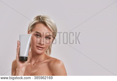 Portrait Of Young Woman With Perfect Fresh Skin Looking At Camera, Holding And Advertising Cosmetic