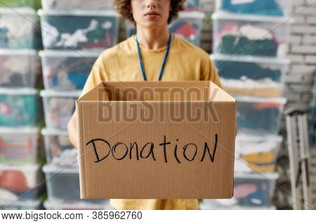 Cropped Shot Of A Guy Holding Donation Box, Posing In Front Of Boxes Full Of Clothes, Young Male Vol