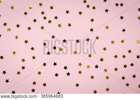 Golden Star Sprinkles On Pink. Festive Holiday Background. Celebration Concept. Top View, Flat Lay.