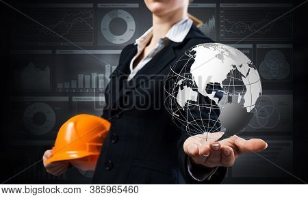 Businesswoman Holds In Palm 3d World Globe. Woman In Business Suit With Orange Safety Helmet. Intern