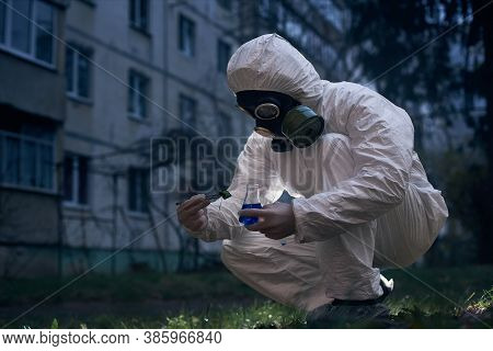 Crouching Researcher Working In Uniform And A Gas Mask, Found A Sample For His Laboratory Study In Z