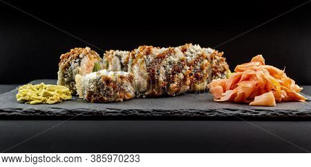 Panoramic Photo Of Served Warm Sushi With Ginger And Wasabi On A Black Stone Plate.