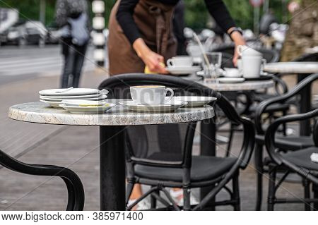 A Table With Uncleared Dishes After Visitors In A Street Cafe With A Waitress In The Background.