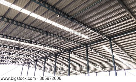 Roof Steel Beam Structure In Industrial Factory, Background Of Factory Ceiling With One Light Blub,