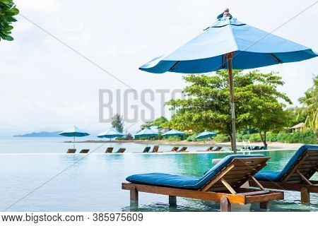 Beautiful Tropical Beach Scenery With Two Beach Bed With Umbrella On The Swimming Pool. Luxury Resor