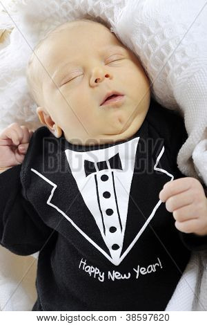 """Close-up of a sleeping newborn boy dressed in a black """"tux"""" that welcomes the new year.  On a white background."""
