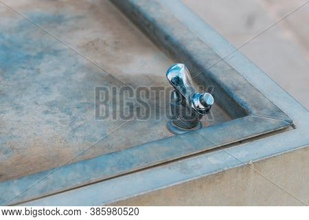 Water Drinking Fountain In Public Area. Close-up View Of Dry Closed Drinking Fountain. Aluminum Dirt