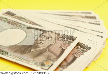 Ten Thousand Yen (10,000 Yen) Banknotes Stacked. Japanese Money. Paper Money. Isolated On Yellow Bac