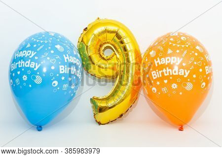Inflatable Numeral 9 Sparkling Metallic Golden Color With Blue And Yellow Balloons Isolated On White