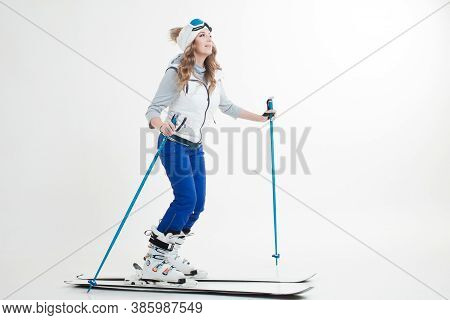 Young Woman Goes Skiing. Skier Maneuvers On Mountain Skis, Photos On A White Background In The Studi