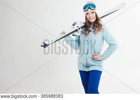 Smiling Woman Skier On A White Background, Portrait In The Studio. A Young Woman In A Blue Jacket Fo