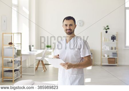 Smiling Man Doctor Chiropractor Or Osteopath Standing With Notes And Looking At Camera