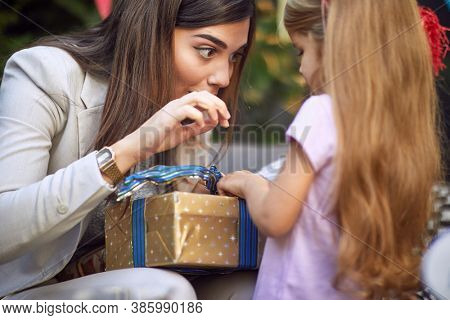 beautiful young adult brunette making funny face while unwrapping birthday present for little caucasian girl