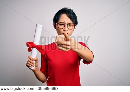 Beautiful chinese student woman wearing glasses holding university graduated diploma degree pointing with finger to the camera and to you, hand sign, positive and confident gesture from the front