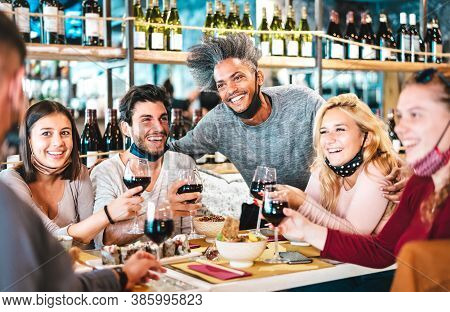 Friends Drinking Red Wine At Sushi Bar Restaurant With Open Face Masks - New Normal Lifestyle Concep