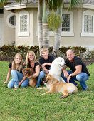 happy and attractive family with their dogs on front lawn at home poster