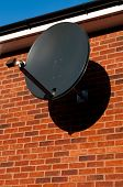 black satellite dish attached to brick wall (residential house copy-space available) poster