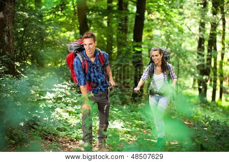 Young beautiful couple in a forest, hiking at summertime.  poster