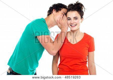 Handsome boy talking secret to young girl in her ear girl laughing over isolated white background poster