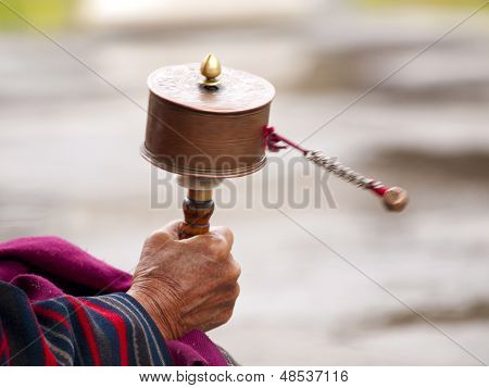 An Older Women Spinning Her Prayer Wheel