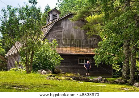 Man Standing By A Vermont Barn