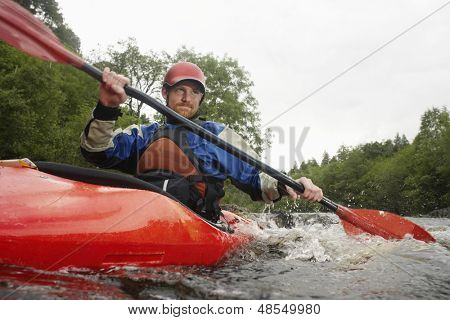 Low angle view of a young man kayaking in river poster