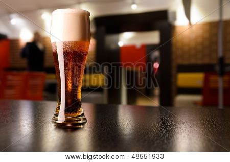 glass of fresh draft lager beer on table in pub