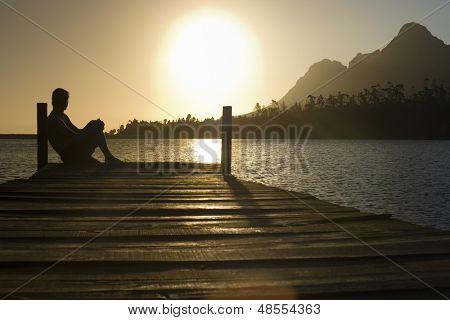 Vista lateral del hombre sentado en muelle por el lago, disfrutando del atardecer
